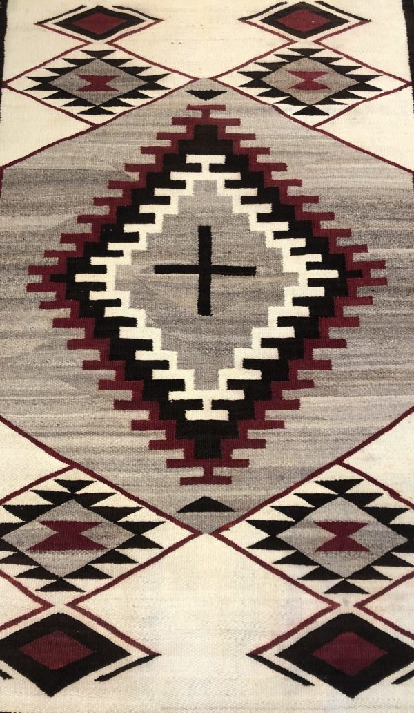 Here is a great double Navajo blanket with a neat design of diamonds and a cross in the middle. This rug is not in perfect condition, but presentable. It has had some cleaning.
