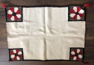 Description: A 1940s Navajo Single Saddle Blanket with four flowers. This is a nice piece in overall good condition but does have some light staining and appears to have a few missing tassels on a couple of the corners.